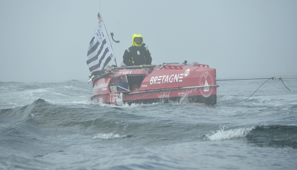 Guirec Soudee is towed through some choppy water to start his journey from Chatham, Mass., to France in his ocean rowboat, Romane on June 15.