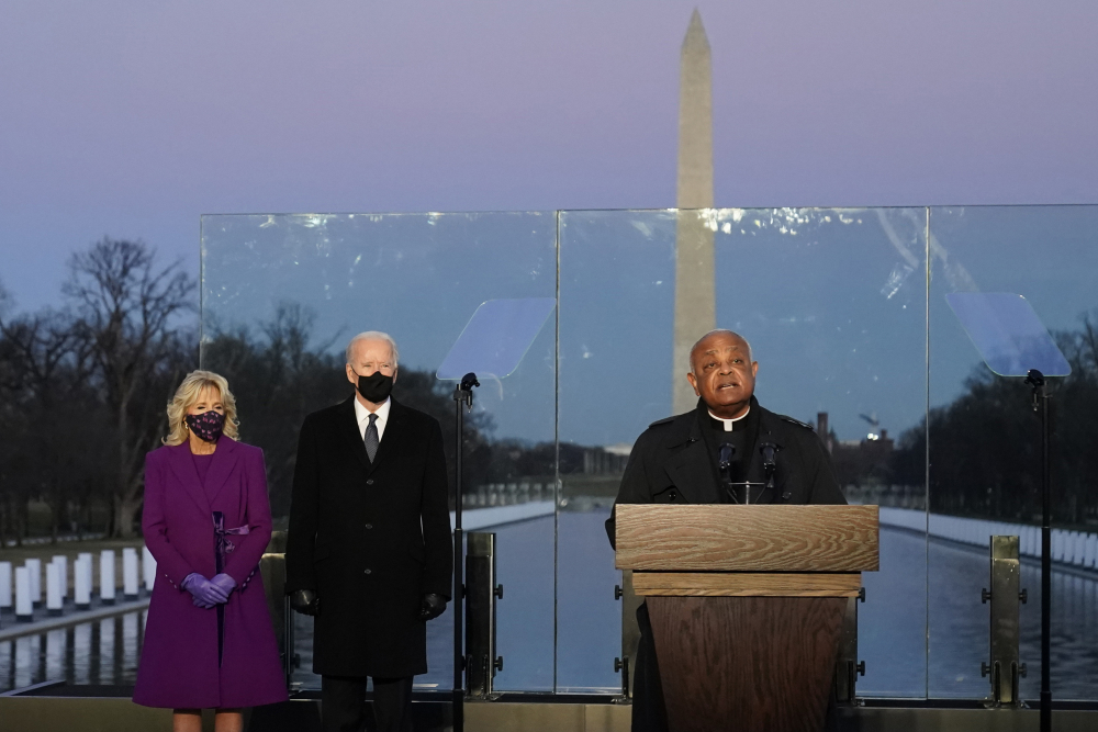 In January, then President-elect Joe Biden and his wife, Jill, listen as Cardinal Wilton Gregory, Archbishop of Washington delivers the invocation during a COVID-19 memorial at the Lincoln Memorial Reflecting Pool in Washington. Gregory has made clear that Biden, who sometimes worships in Washington, is welcome to receive Communion at the archdiocese's churches.