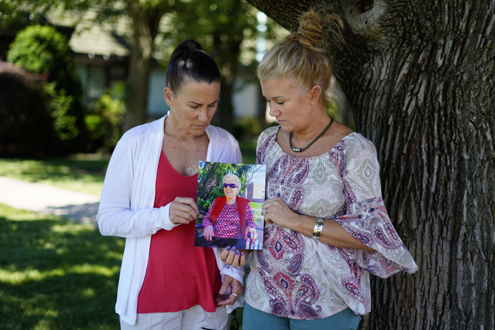 """Angela Ermold, right, and her sister, Denise Gracely, hold a photo of their mother, Marian Rauenzahn, on Thursday in Fleetwood, Pa. """"They have protected them to death,"""" Gracely says."""