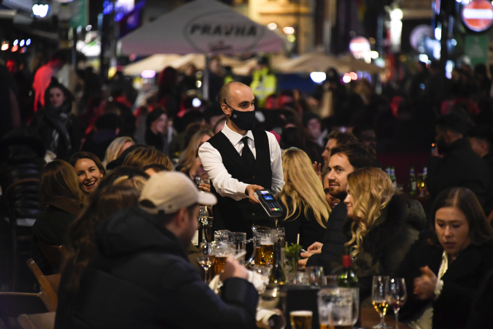 Awaiter wears a face mask as people eat and drink outside restaurants in Soho, in London, on Nov. 4, 2020. British Prime Minister Boris Johnson is expected to confirm Monday June 14, 2021, that the next planned relaxation of coronavirus restrictions in England will be delayed as a result of the spread of the delta variant first identified in India.