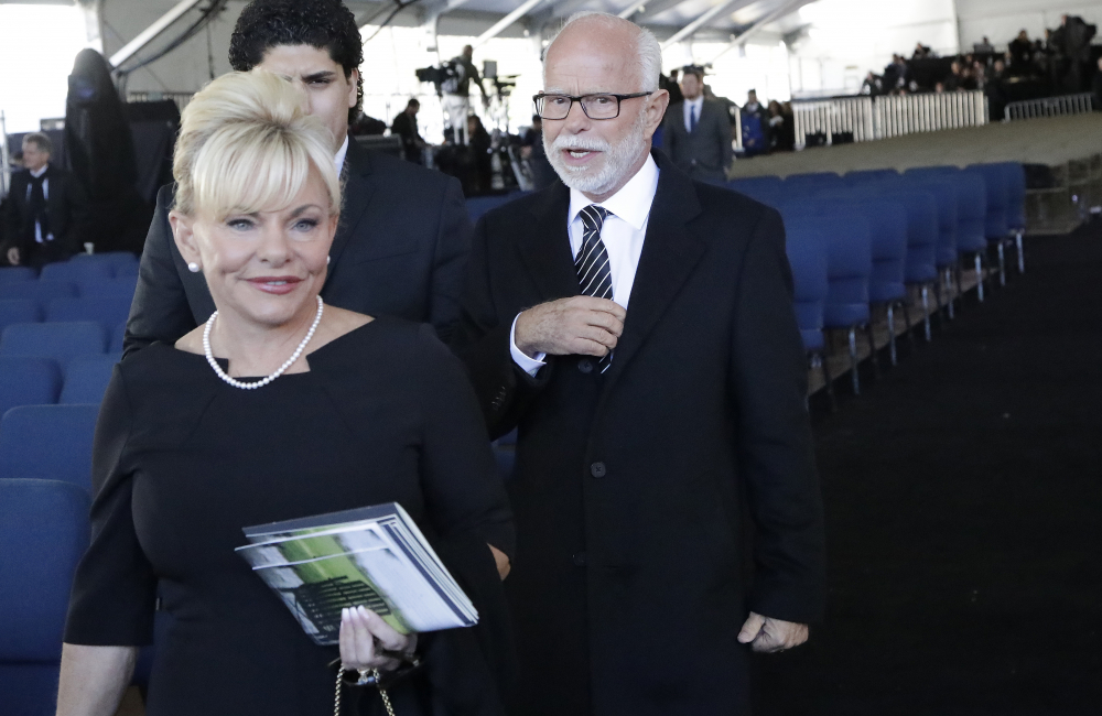Televangelist Jim Bakker, right, walks with his wife Lori Beth Graham after a funeral service at the Billy Graham Library for the Rev. Billy Graham, in Charlotte, N.C. in 2018. Jim Bakker and his southwestern Missouri church will pay restitution of $156,000 to settle a lawsuit that accused the TV pastor of falsely claiming that a health supplement could cure the coronavirus.
