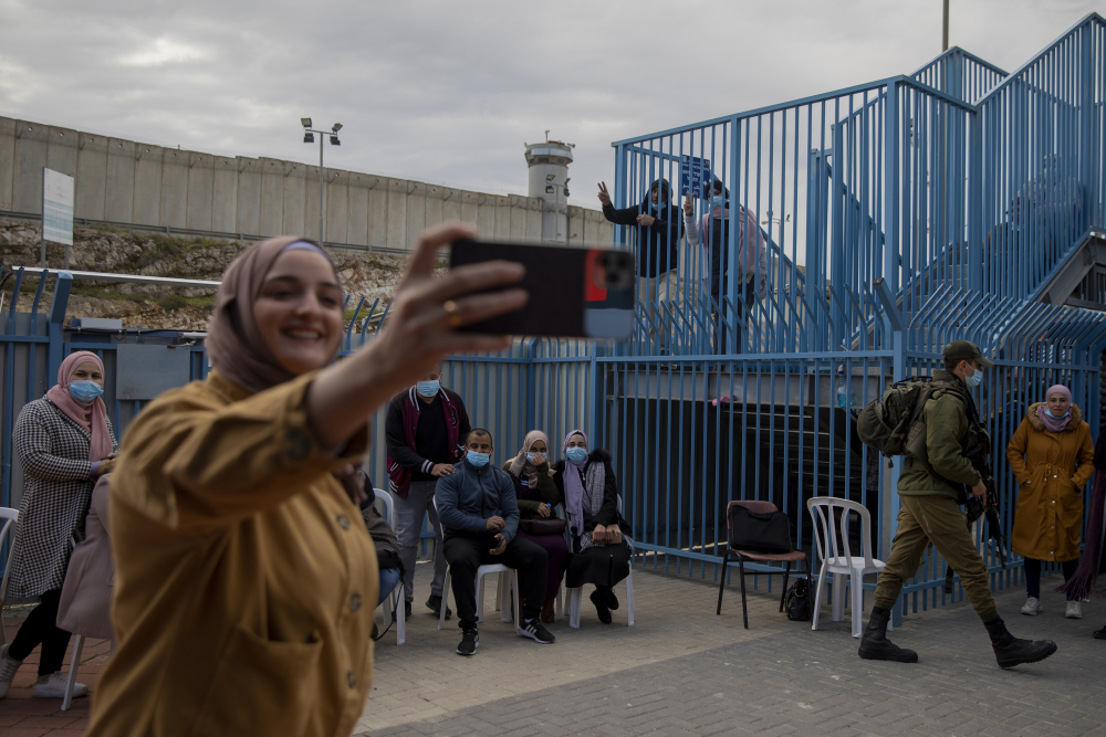Palestinians take a selfie after receiving the coronavirus vaccine from an Israeli medical team at the Qalandia checkpoint between the West Bank city of Ramallah and Jerusalem in February.