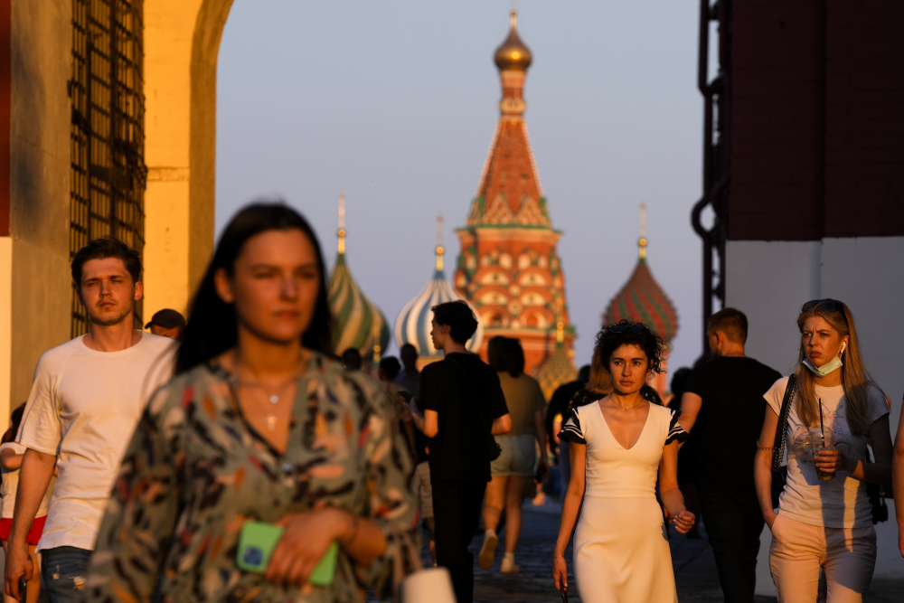 People, most of them without face masks, walk at Red Square during sunset in Moscow on Thursday, June 24.