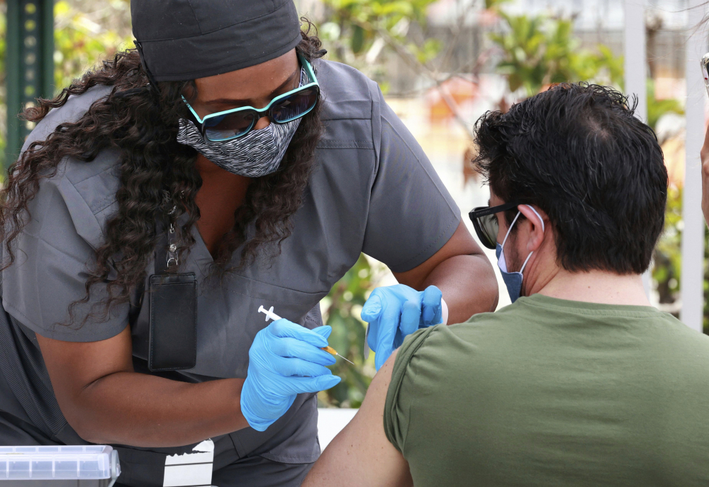An Orange County resident receives the COVID-19 vaccine at a mobile vaccination site at Camping World Stadium in Orlando, Fla., on Thursday. U.S. demand for shots has slumped.