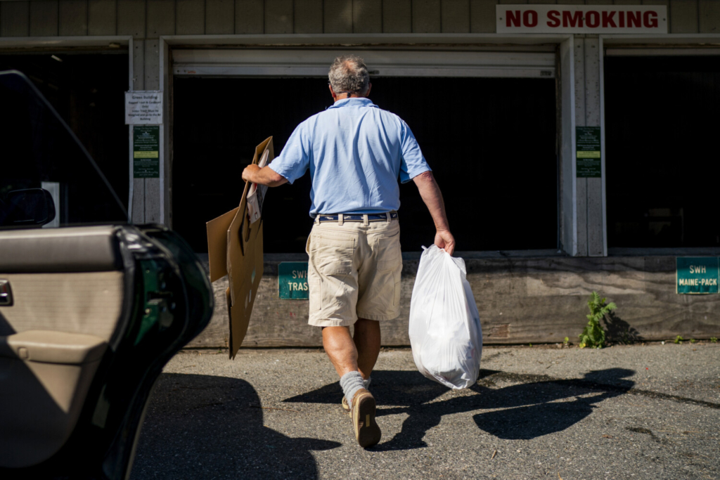 John Maxwell walks cardboard and garbage from his Subaru to a large bin at Eastern Maine Recycling Inc. in Southwest Harbor. Maxwell and many other residents still sort their recycling out by item, even though the facility stopped recycling all products in recent years.