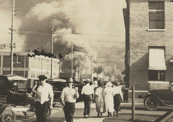 Two armed men walk away from burning buildings as others walk in the opposite direction during the June 1, 1921, race massacre in Tulsa, Okla.