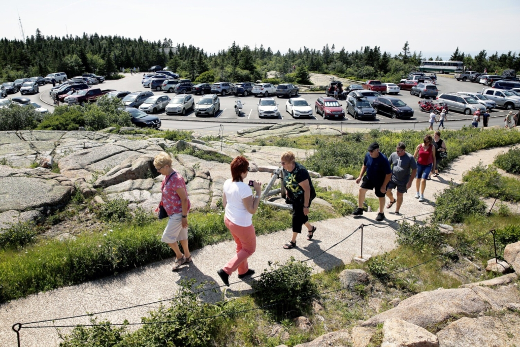 Park visitors ascend a short path from a parking lot to the summit of Cadillac Mountain, one of the most popular spots in Acadia National Park, this month. Space is so limited in the lot that the mountain road is sometimes closed during peak hours.
