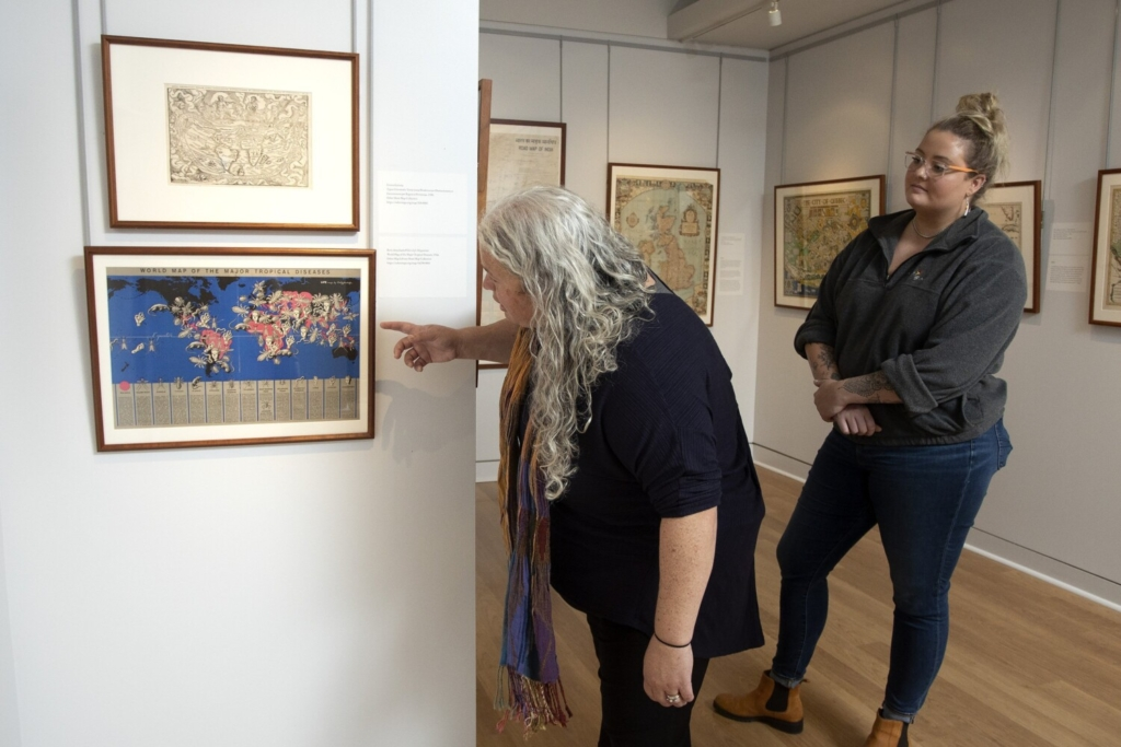 """Morgan Day looks on as Libby Bischof, points out  a world map of tropical diseases from 1944, part of the exhibit """"Where Will We Go From Here? Travel in the Age of COVID-19"""" at the Osher Map Library in Portland."""