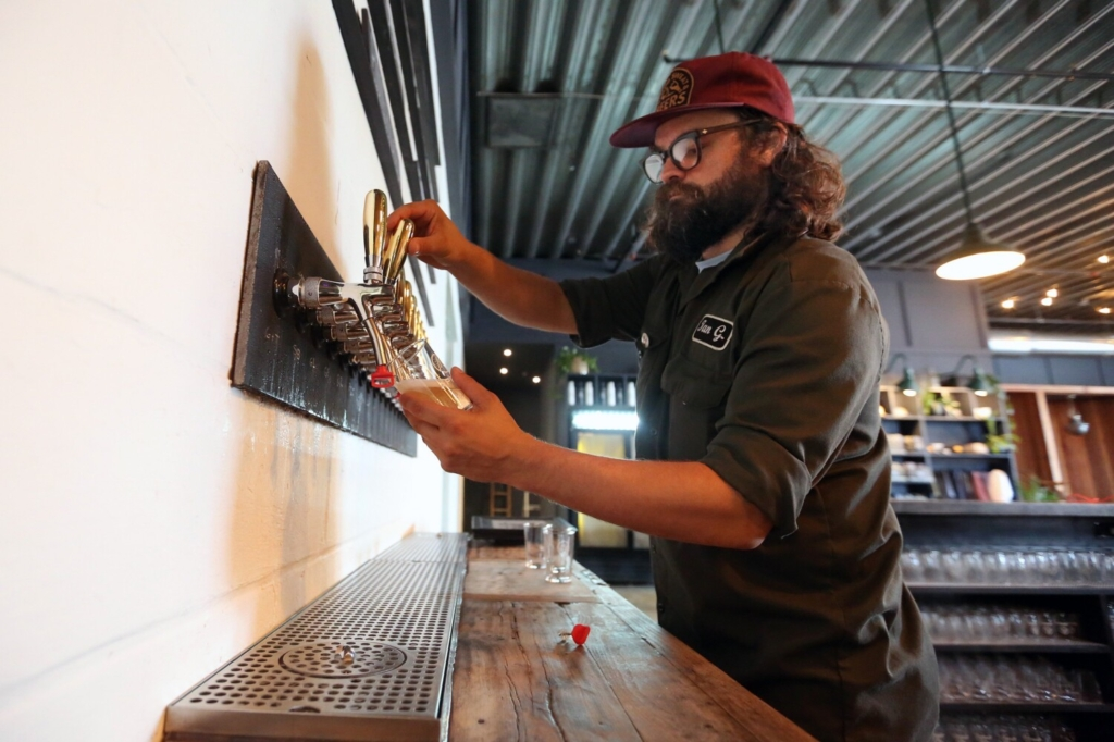 Ian Goering, head of production at Apres in Portland, draws a glass of hard seltzer from a tap. Hard seltzers are here, there and everywhere in Maine lately.
