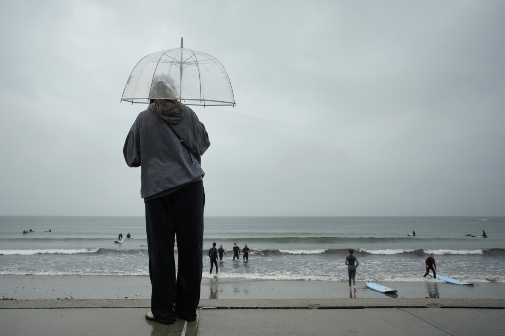 Jenny Shanley holds an umbrella to shield herself from a driving rain while watching a surfing class at Gooch's Beach in Kennebunk on Friday. Despite the rain, drought conditions persist in Maine.