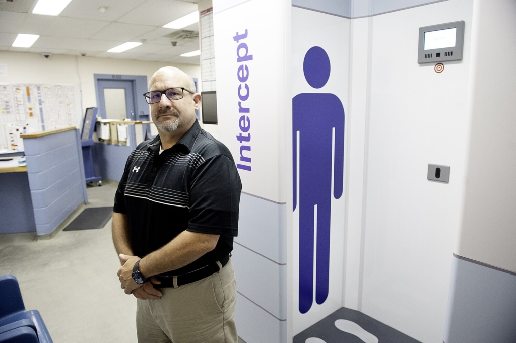 Androscoggin County Jail Administrator Jeff Chute stands Thursday next to the full body scanner that detects drugs, weapons and other contraband on inmates and incoming packages at the facility in Auburn.