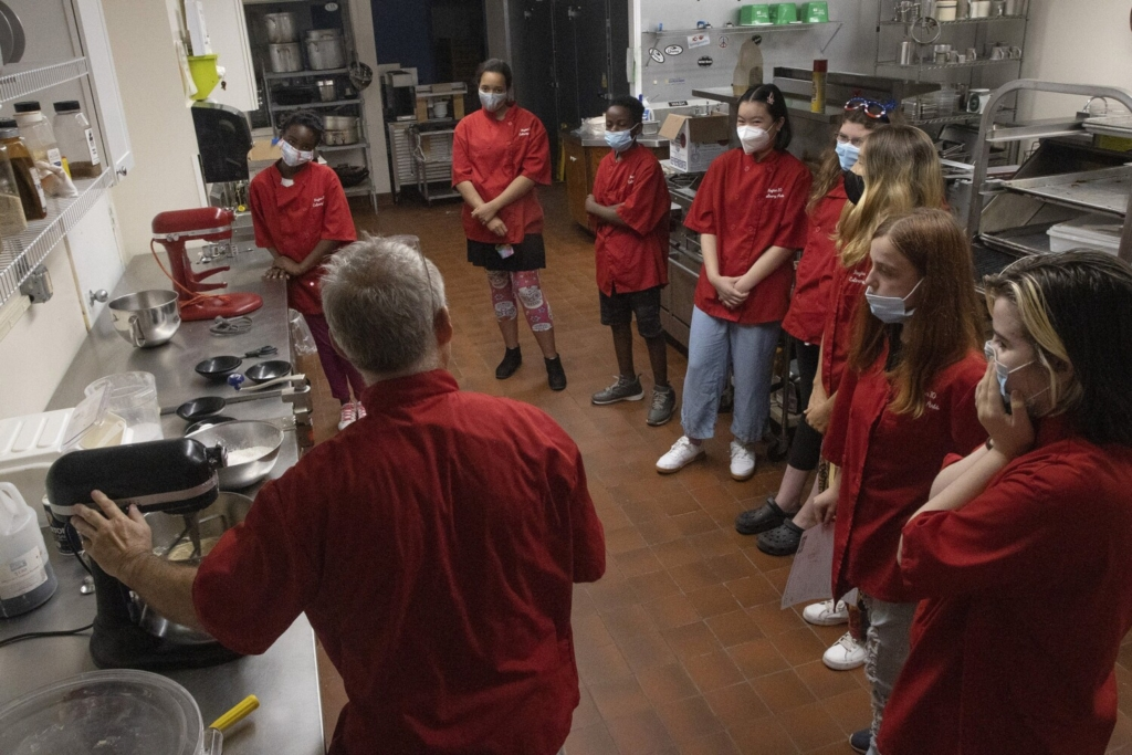 Students watch culinary arts instructor Tim Dean last week as he demonstrates the process of making chocolate chip cookies during a technical education summer camp at Region 10 Technical High School in Brunswick.
