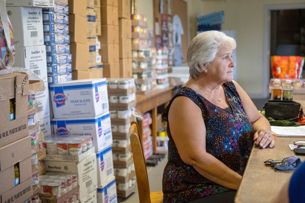 Anne Hodgdon takes a break from stocking the shelves at the food pantry inside St. John's church in Winslow on Wednesday.