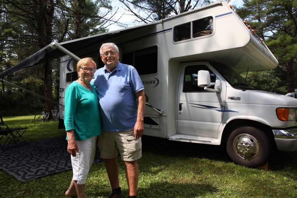 Diane and Roger Lavertu of Lewiston stand by their recreational vehicle at Winslow Park and Campground in Freeport. The couple wanted a shoreline campsite, but ended up with a site in the trees.
