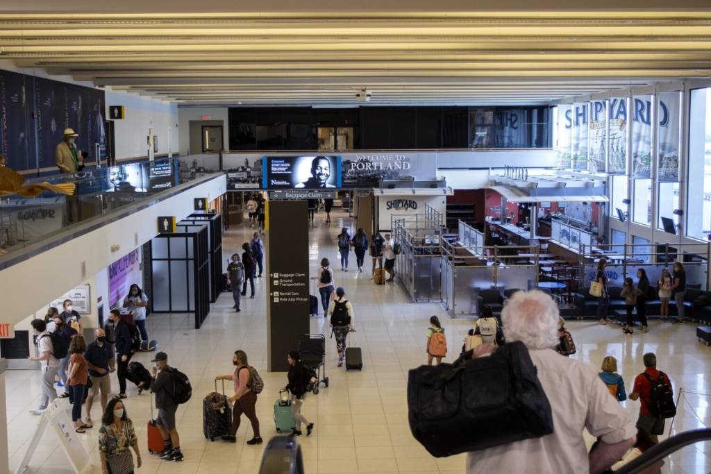 Travelers move through the Portland International Jetport on Wednesday after arriving in Maine. The airport is on track for record numbers of passengers summer despite the lingering coronavirus pandemic.