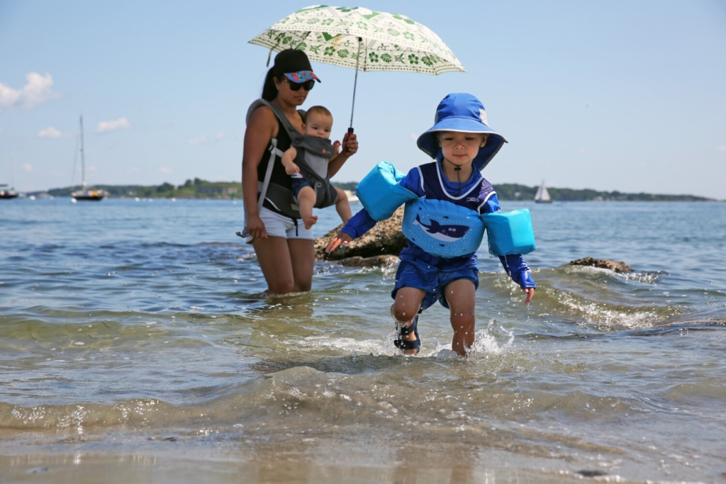 Desmond Predick, 3, emerges from the water with his mother, Jenny Predick, and brother David on Friday at Willard Beach in South Portland.