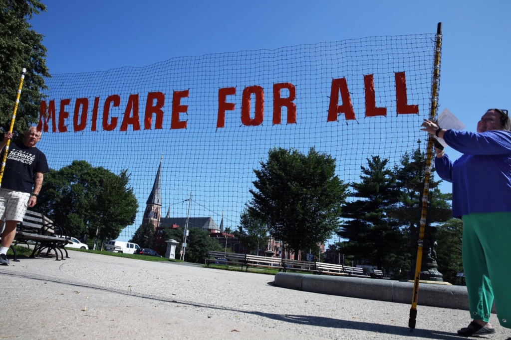 Bill Weber of Portland and Marie Follayttar of South Portland unfurl a see-through banner at the start of a rally at Lincoln Park in Portland on Saturday as part of a national effort to demand improved and expanded Medicare for everyone. Follayttar is the director of Mainers for Accountable Leadership.