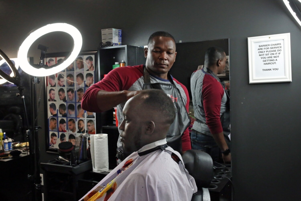 Joe Etienne cuts Christian Muhitira's hair at Major Cuts in Lewiston on Thursday. Both men said they would comply with new guidelines from Maine and the federal CDC on mask wearing in areas of high transmission.