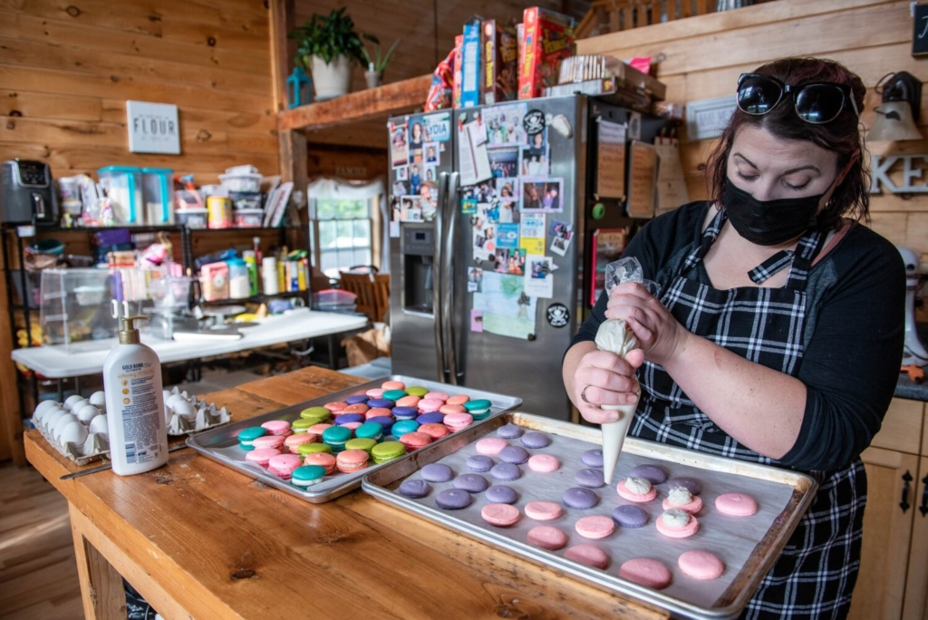 Jenna Roberts fills pink macarons Saturday at her home-based bakery, Marvelous Macarons in Lewiston, for the Bakes for Breast Cancer fundraiser.