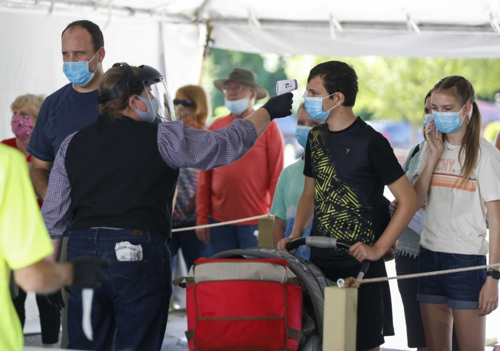 A Silver Dollar City employee takes the temperature of guests before they are allowed to enter the park just west of Branson, Mo., in June. Greene County, Mo., reported 19 COVID-19 deaths in June, virtually all caused by the delta variant. Deaths are expected to double or triple in July.