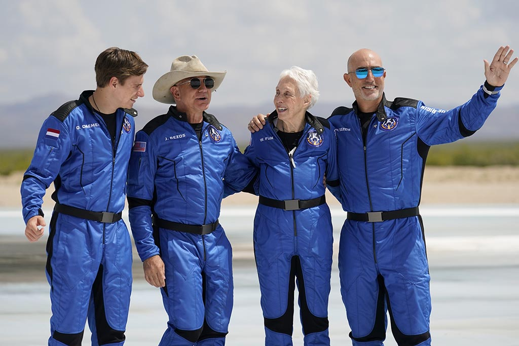 From left, Oliver Daemen, Jeff Bezos, founder of Amazon and space tourism company Blue Origin, Wally Funk and Bezos' brother Mark pose for photos in front of the Blue Origin New Shepard rocket after their launch from the spaceport near Van Horn, Texas, on Tuesday.