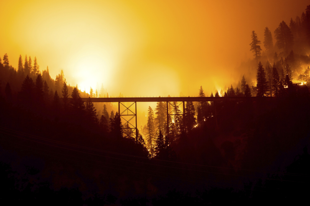 The Dixie Fire burns behind a bridge in Plumas County, Calif., on Sunday. More than 7,500 people were under evacuation orders in Plumas and Butte counties as of Friday.