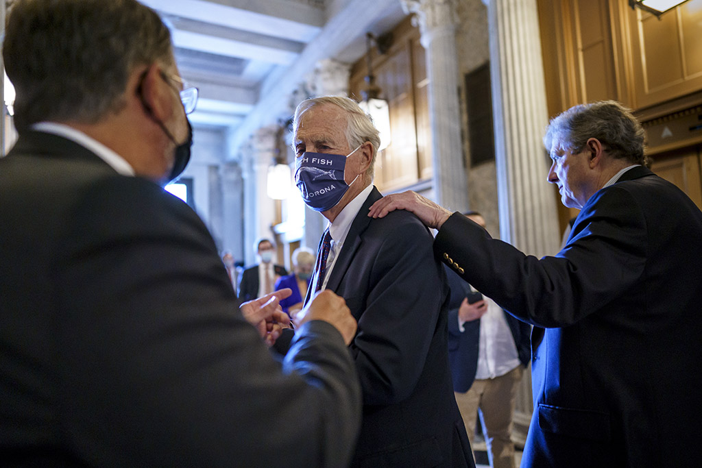 Sen. Angus King of Maine, center, speaks with Sen. Gary Peters, D-Mich., left, while Sen. John Kennedy, R-La., walks by at right, as the Senate votes Friday to formally begin debate on a roughly $1 trillion infrastructure plan.