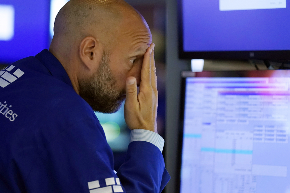 Specialist Meric Greenbaum works on the floor of the New York Stock Exchange on Monday. Stocks were falling sharply Monday as worries sweep from Wall Street to Sydney that the worsening pandemic in hotspots around the world will derail what's been a strong economic recovery.