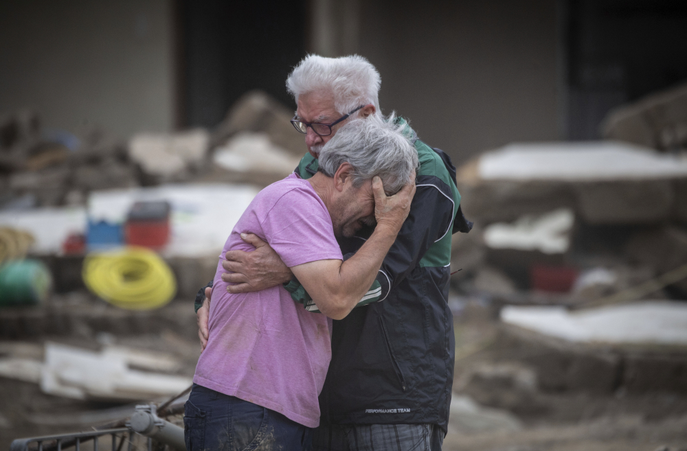 Two brothers weep Monday in front of their parents' house, which was destroyed by the flood in Altenahr, Germany.