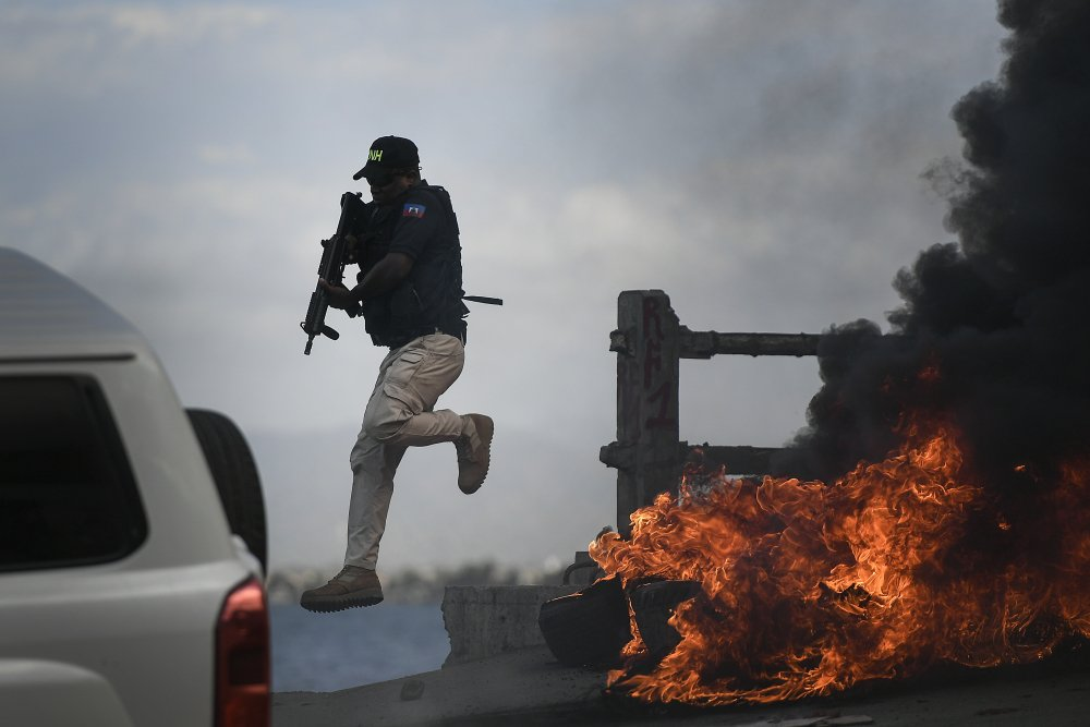A police officer abandons his vehicle during a demonstration Thursday that turned violent in which protesters demanded justice for the assassinated President Jovenel Moise in Cap-Haitien, Haiti.
