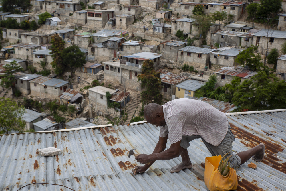 Antony Exilien secures the roof of his house in response to Tropical Storm Elsa, in Port-au-Prince, Haiti, on Saturday. Elsa brushed past Haiti and the Dominican Republic on Saturday and threatened to unleash flooding and landslides before taking aim at Cuba and Florida.