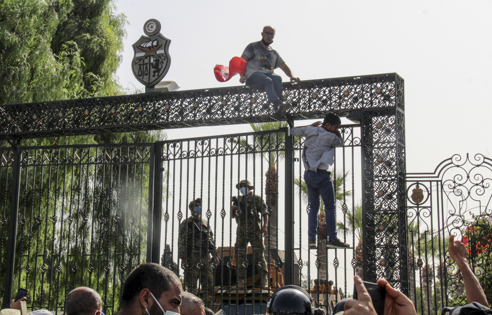 Tunisian soldiers guard the main entrance of the parliament as demonstrators gather outside in Tunis, Tunisia, on Monday.