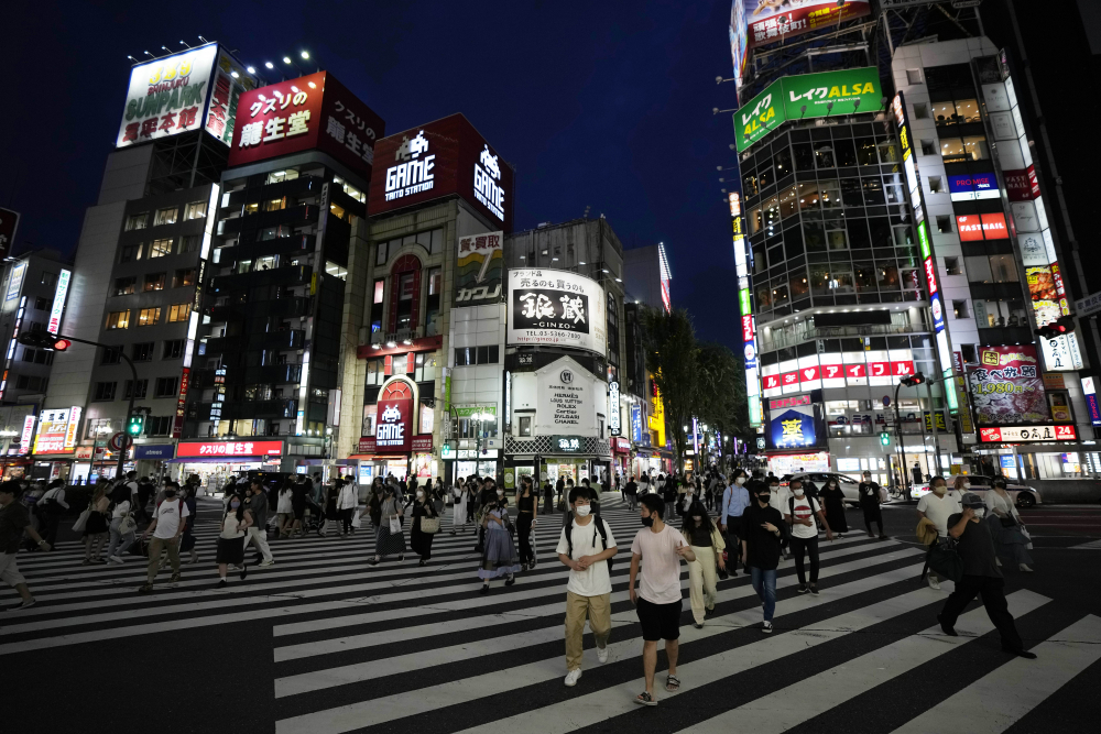 People walk along a pedestrian crossing Friday, July 30, 2021, in Tokyo, as Japanese Prime Minister Yoshihide Suga expanded a coronavirus state of emergency to four more areas in addition to Tokyo following record spikes in infections as the capital hosts the Olympics.