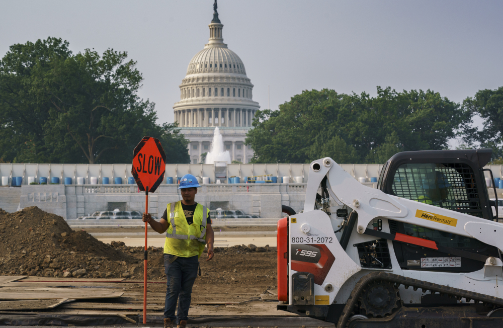 Workers repair a park near the Capitol in Washington on Wednesday as senators struggle to reach a compromise over how to pay for nearly $1 trillion in public works spending, a key part of President Biden's agenda.