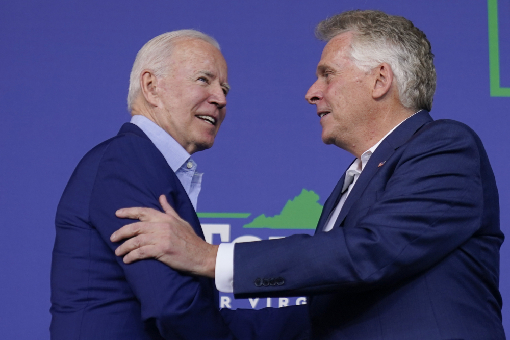 President Biden greets Virginia Democratic gubernatorial candidate Terry McAuliffe as he arrives to speak at a campaign event for McAuliffe at Lubber Run Park Friday in Arlington, Va.