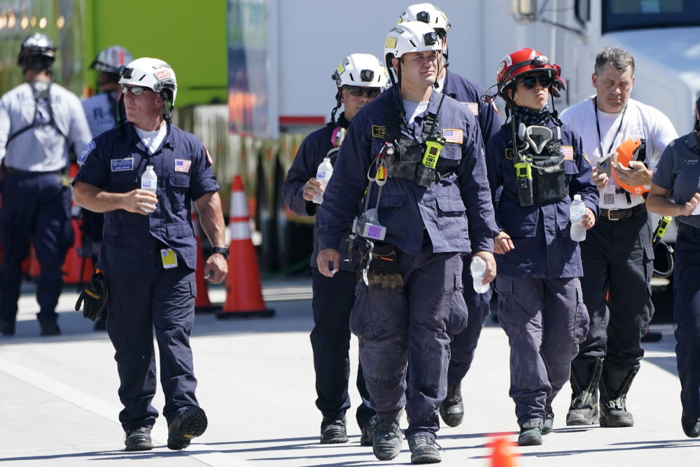 Members of the South Florida Urban Search and Rescue team walk near the Champlain Towers South condo building, where scores of victims remain missing more than a week after it partially collapsed, Saturday in Surfside, Fla.