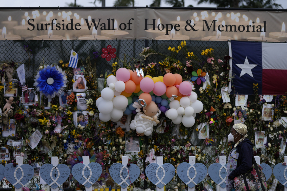 A woman walks past a makeshift memorial for the victims of the Champlain Towers South building collapse, on Monday, July 12, in Surfside, Fla.