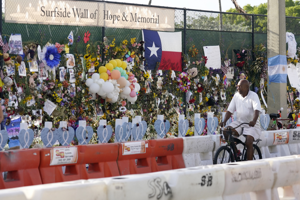A cyclist rides past a makeshift memorial recognizing the victims of the partially collapsed Champlain Towers South building, as removal and recovery work continues at the site, Tuesday, July 13, in Surfside, Fla.