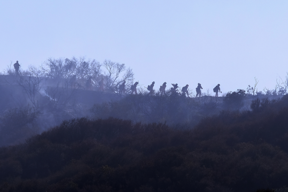 A hotshot hand crew walks in line during a wildfire in Topanga, west of Los Angeles, on Monday. A brush fire scorched about 15 acres in Topanga, initially threatening some structures before fire crews got the upper hand on the blaze.