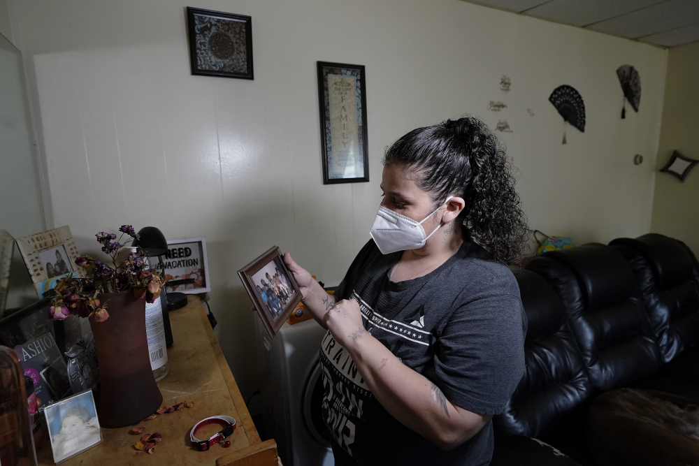 Roxanne Schaefer holds a photograph in the living room of her apartment, in West Warwick, R.I., on Tuesday.