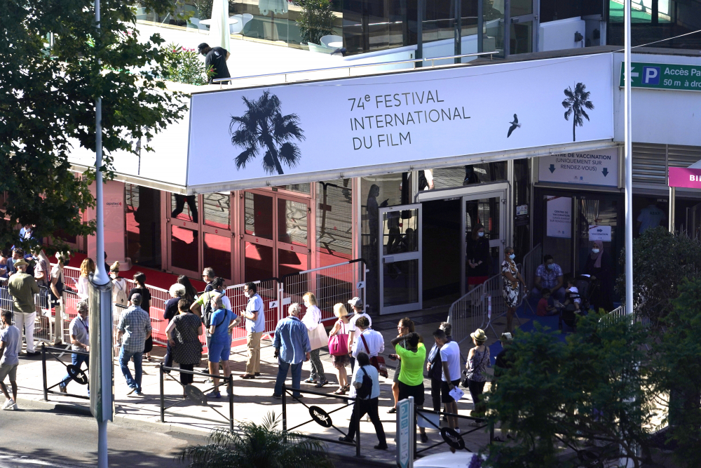 Members of the public walk in front of the Palais des Festival on Monday prior to the 74th international film festival, Cannes, southern France. The Cannes film festival runs from July 6 - July 17.
