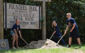 From left, Wells Elementary School students Vienna Cardinali, Emma Herman, and Robert Roche prepare to bury a time capsule, including various items reflective of their generation and on student life during the pandemic years of 2020-2021.