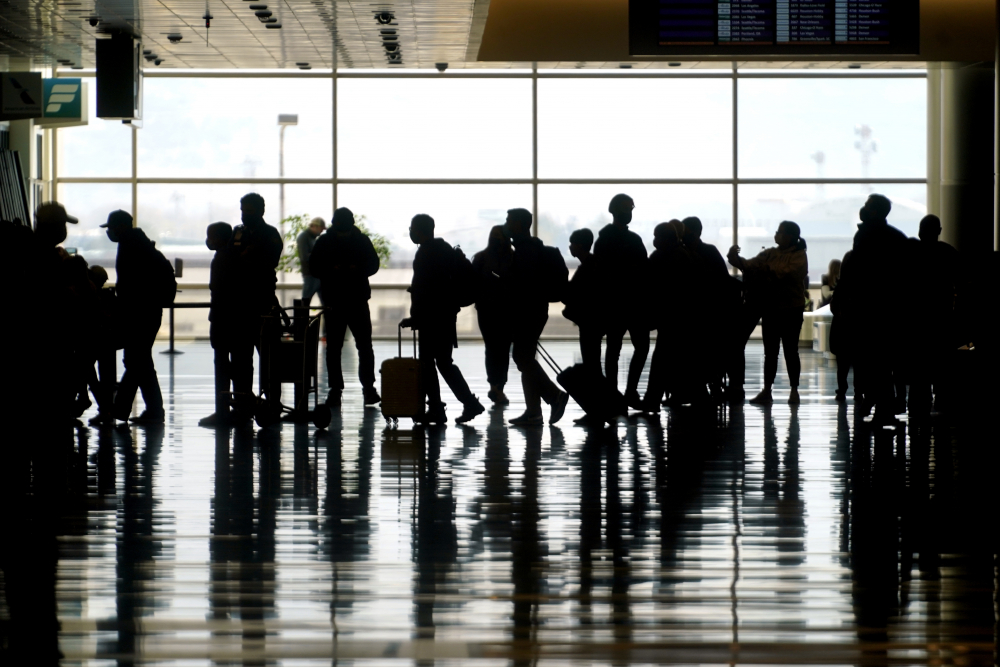 Travelers walk through the Salt Lake City International Airport in Salt Lake City in March. The U.S. will keep existing COVID-19 travel restrictions on international travel in place for now.
