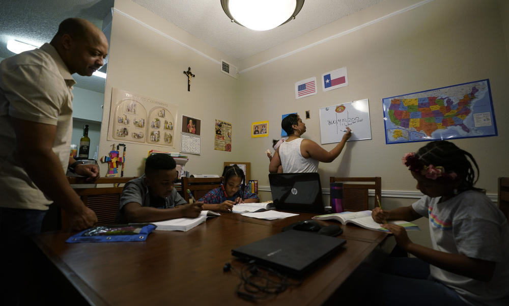 """Arlena Brown, center, holds her youngest child, Lucy, 9 months, as she and husband, Robert, left, lead their other children, from left, Jacoby, 11; Felicity, 9, and Riley, 10, through math practice Tuesday at their home in Austin, Texas. """"I didn't want my kids to become a statistic and not meet their full potential,"""" said Robert, a former teacher who now does consulting. """"And we wanted them to have very solid understanding of their faith."""""""