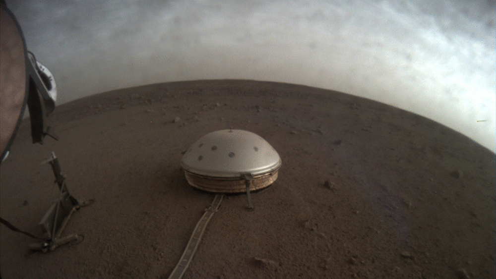 Clouds drift over the dome-covered SEIS seismometer of the InSight lander on the surface of Mars. The quake-measuring device is providing the first detailed look at the red planet's interior, revealing a surprisingly thin crust and a molten core.