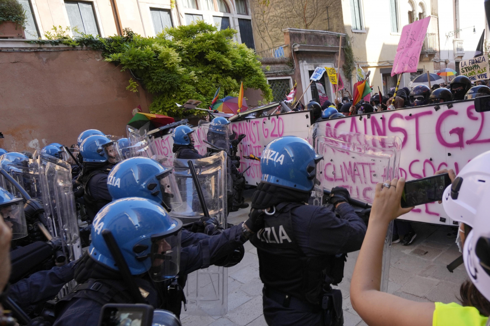 Italian police in riot gear clash with demonstrators during a protest against the G-20 meeting in Venice, Italy, on Saturday.