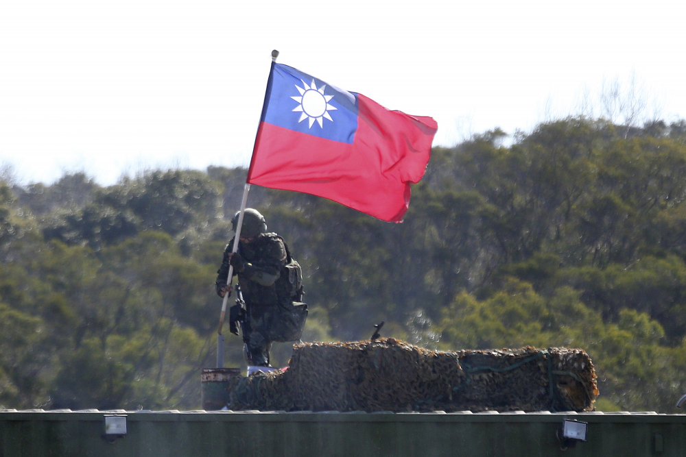 A soldier holds a Taiwanese flag during a military exercise aimed at repelling an attack from China in Hsinchu County, northern Taiwan in January.