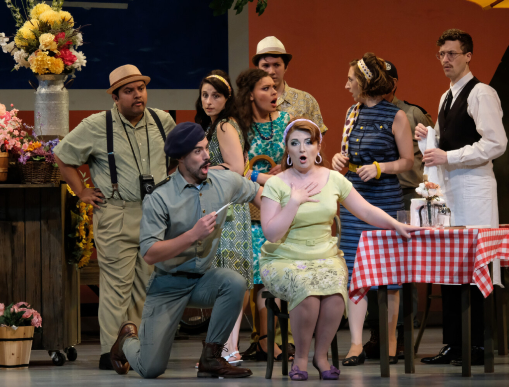 """Luis Orozco as Belcore, kneeling, and Sarah Tucker as Adina, sitting, with the ensemble of """"The Elixir of Love."""""""