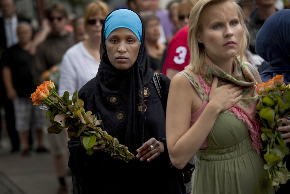 On July 24, 2011, women carry flowers as they arrive for a memorial service at Oslo Cathedral in the aftermath of the bombing and shooting attacks on Norway's government headquarters and a youth retreat, in Oslo.
