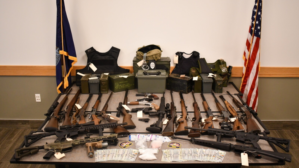 Police seized 36 firearms, thousands of rounds of ammunition and fake police identification, among other items, from a home in Old Orchard Beach on Sunday.